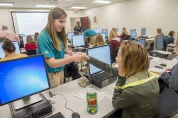 UNCW female student helping another female student at a computer