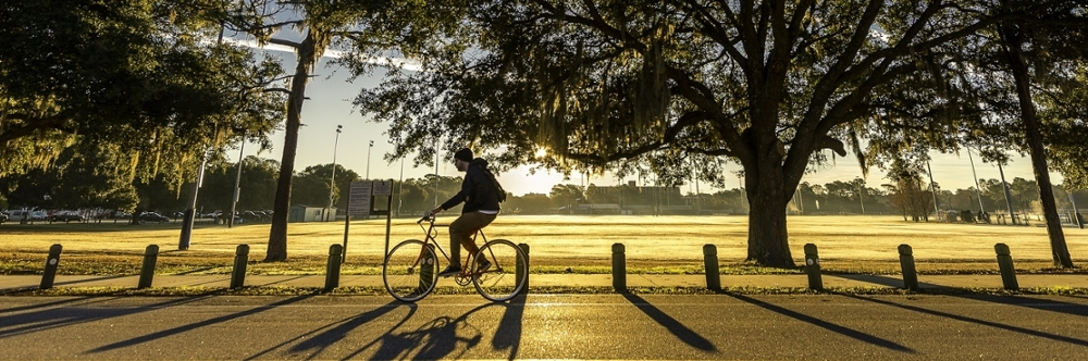Student riding their bike on campus at sunrise