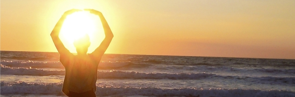 Student doing yoga pose on beach at sunset